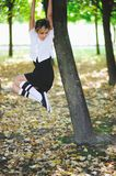 Attractive young girl hanging on the tree. In autumn park Stock Images