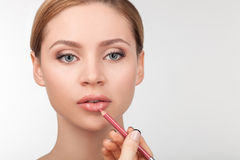 Attractive young girl is having her face pained Stock Photos
