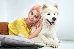 Attractive young girl with her pet Samoyed posing lying on the white floor. Studio portrait with gentle warm tones. stock photo