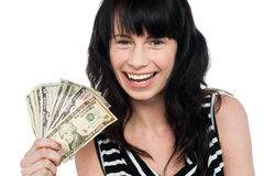 Attractive young girl holding currency fan Royalty Free Stock Photo
