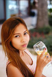Attractive young girl holding a glass and drinking martini with lemon cocktail Stock Image