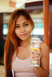 Attractive young girl holding a glass and drinking martini with lemon cocktail Stock Photos