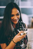 Attractive young girl holding a glass and drinking martini with lemon cocktail stock photography