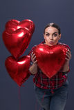 Attractive young girl holding Valentine`s Day heart balloon Royalty Free Stock Images