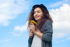 Attractive, young girl in jeans and a black hat holding a blooming dandelions. Royalty Free Stock Photo