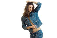 Attractive young girl in jeans jacket raised a hand up lowered her head and posing for the camera. On white background Stock Photos