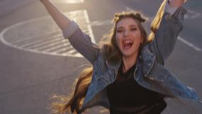 Attractive young girl in jeans jacket, with very long hair laughing, jumping and running, turns to camera and smiles. Happily. Cheerful mood, being happy stock footage