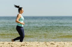 Attractive young girl jogging on a beach in the summer Stock Photography