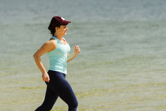 Attractive young girl jogging on a beach in the summer Stock Images