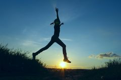 An Attractive Young Girl Jumping In The Air At The Sunset. stock photo