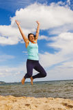 Attractive young girl jumping on a beach in the summer Stock Image