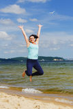 Attractive young girl jumping on a beach in the summer Royalty Free Stock Photography