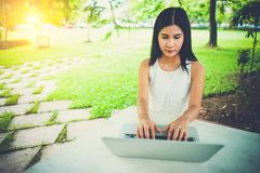 Attractive young girl with laptop outdoors. woman working. Royalty Free Stock Photo