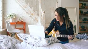 Attractive young girl learning to play electric guitar with notebook sit on bed in bedroom at home. Indoors Royalty Free Stock Photo