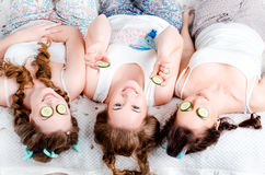 Attractive young girl lying on the bed on the back of the two gi. Rls in front of a cucumber slices, they smile. Friendship. Hen-party. Pajama party Royalty Free Stock Image