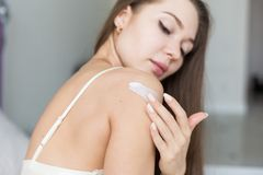 Attractive young girl in night clothes applies cream to skin and rubs it while doing morning procedures. Moisturizing royalty free stock photo