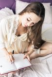 Attractive young girl in a nightgown is sitting in bed and writing into a notebook. royalty free stock photo