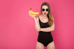Attractive young girl open her mouth and holding bananas Royalty Free Stock Photo