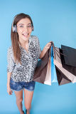 Attractive young girl with packages and earphones Stock Photography