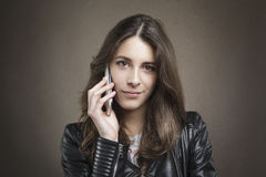 Attractive young girl at phone looking at camera on texture back Stock Images