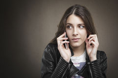 Attractive young girl at phone on texture background. Royalty Free Stock Photo