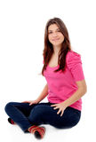 Attractive young girl in pink sitting on the floor Stock Images