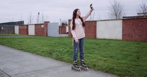 Attractive young girl in pink vest with headphones doing selfie in front of brick fence. Red Epic camera shot in 4k. HD stock video footage