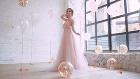 Attractive young girl posing for the camera for a professional photographer, in a light chic long dress in pink and. Violet tones, while golden balloons fall to stock video