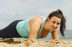 Attractive young girl practicing physical exercises on a beach in the summer Royalty Free Stock Photos