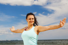 Attractive young girl practicing physical exercises on a beach in the summer Stock Image