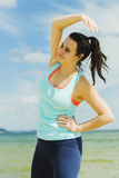 Attractive young girl practicing physical exercises on a beach in the summer Royalty Free Stock Image