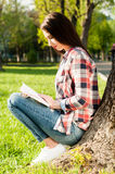 Attractive young girl reading a book on nature near tree Royalty Free Stock Image