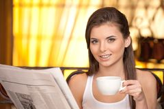 Attractive young girl reading newspaper. Stock Image