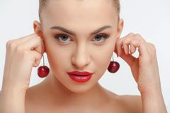 Attractive young girl with red appetite cherry Stock Image