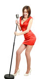 Attractive young girl in a red dress singing into a microphone Royalty Free Stock Photography