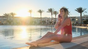 Attractive young girl in red swimsuit talking on the smartphone near the swimming pool. Bikini girl having good time on stock footage
