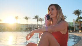 Portrait of attractive young girl in red swimsuit talking on the smartphone near the swimming pool. Bikini girl having stock video footage