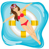 Attractive young girl relaxing in swimming pool  floating on an inflatable ring Stock Photo
