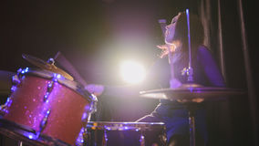 Attractive young girl rock musician - female drummer performing. Telephoto royalty free stock images