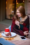 Attractive young girl sitting in a cafe hiding behind a warm blanket. Outside. In the autumn. stock photo