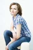 Attractive young girl sitting on the couch home Stock Image