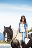 Attractive Young girl sitting on horse. Against blue sky Royalty Free Stock Photography