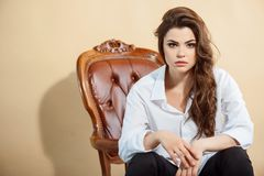 Attractive young girl is situated on chair Stock Image