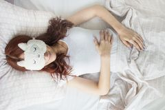 An attractive young girl sleeping in her bed in a sleep mask. View from above royalty free stock photos