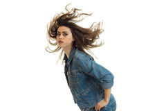 Attractive young girl stands leaning forward and her hair fly through the air. Isolated on white background Royalty Free Stock Photography
