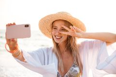 Attractive young girl in summer hat and swimwear. Spending time at the beach, taking a selfie with outsretched hand Stock Photography