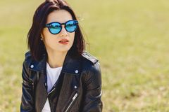 Attractive girl in sunglasses on grass in park. Attractive young girl in sunglasses on grass in park Stock Photos