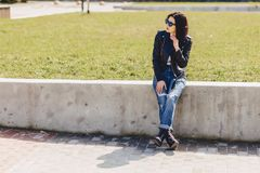 Attractive girl in sunglasses on grass in park. Attractive young girl in sunglasses on grass in park Royalty Free Stock Image