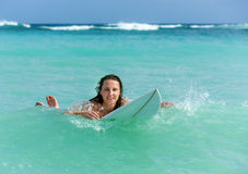 Attractive Young girl on surfboard in ocean Stock Images