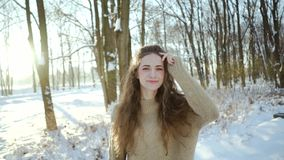 Attractive young girl in a sweater having fun in the cold. Curly young woman in warm clothes on a background of a snowy stock video footage